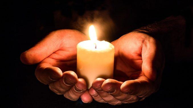 Bild på två händer som håller i ett ljus som brinner
