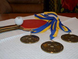 En bild på ett pingisrack och pingisboll som ligger på ett bord tillsammans med tre brons medaljer
