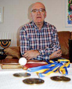 En bild på Christer Eriksson som sitter i soffan med sina tre vinster framför sig på bordet